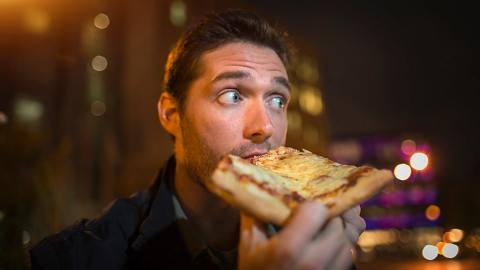 A man eating a large piece of pizza at night