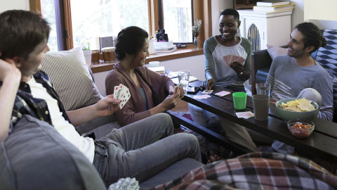 A group of friends playing a card game around a living room coffee table
