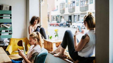 teenage girls using a phone in a cafe