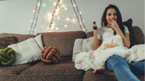 young brunette eating healthy snacks while watching her favourite movie