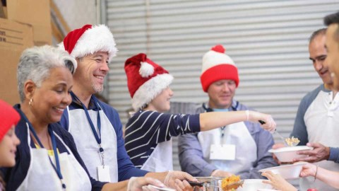 A group of people wearing Christmas hats volunteering at a food bank