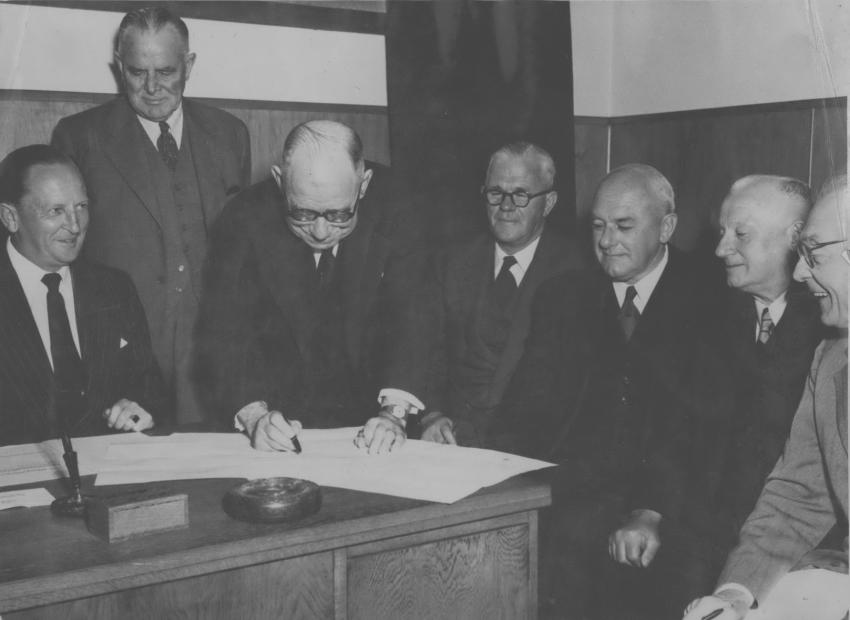 An image of Sir John Allum signing the Bridge contract with colleagues