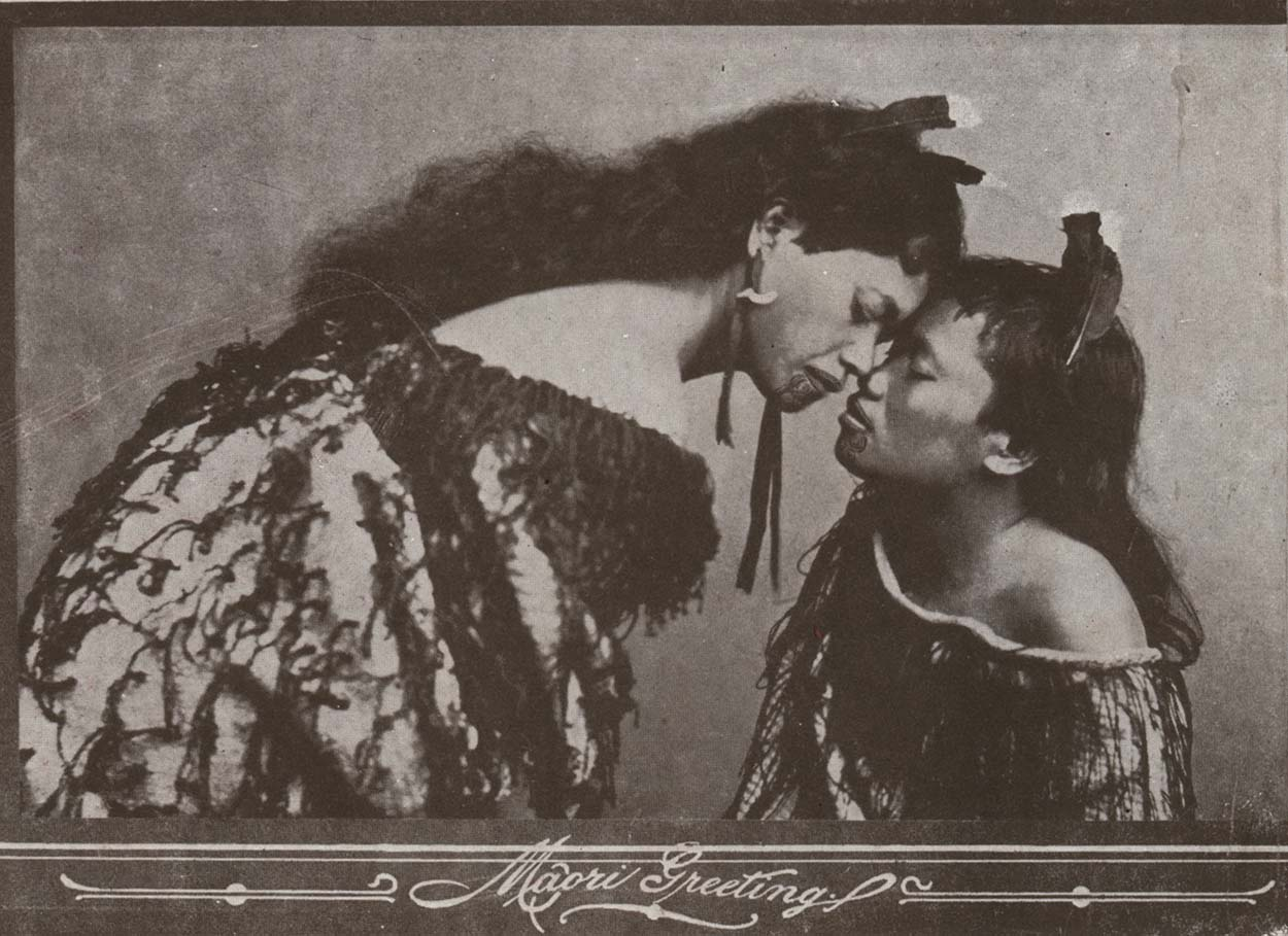 Black and white image of a two Māori women greeting each other with a hongi