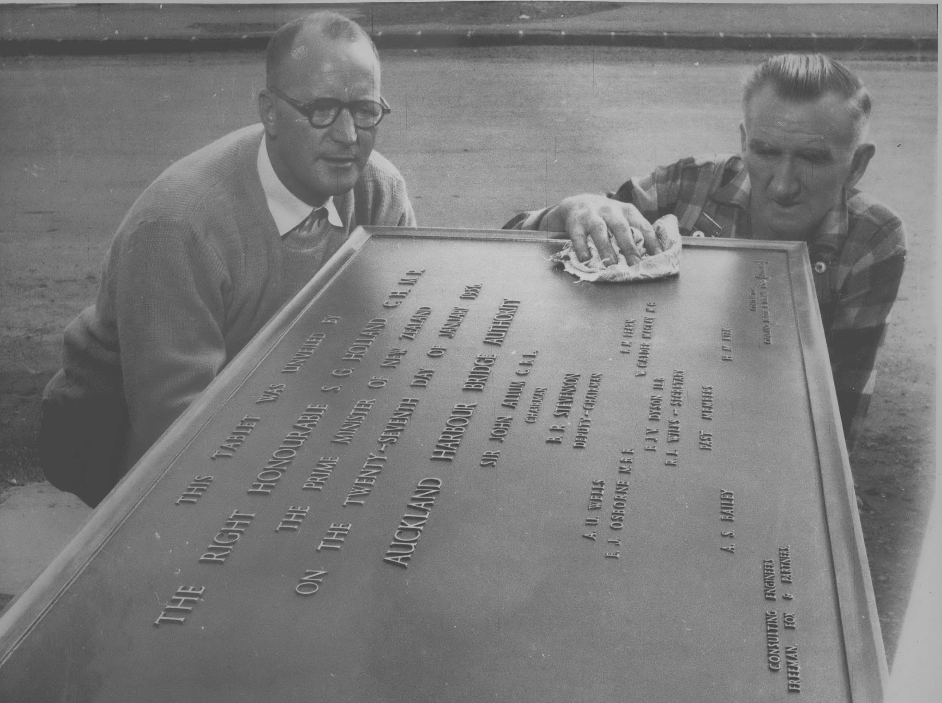 Two men polishing the plaque commemorating the foundation stone laying at the bridge.