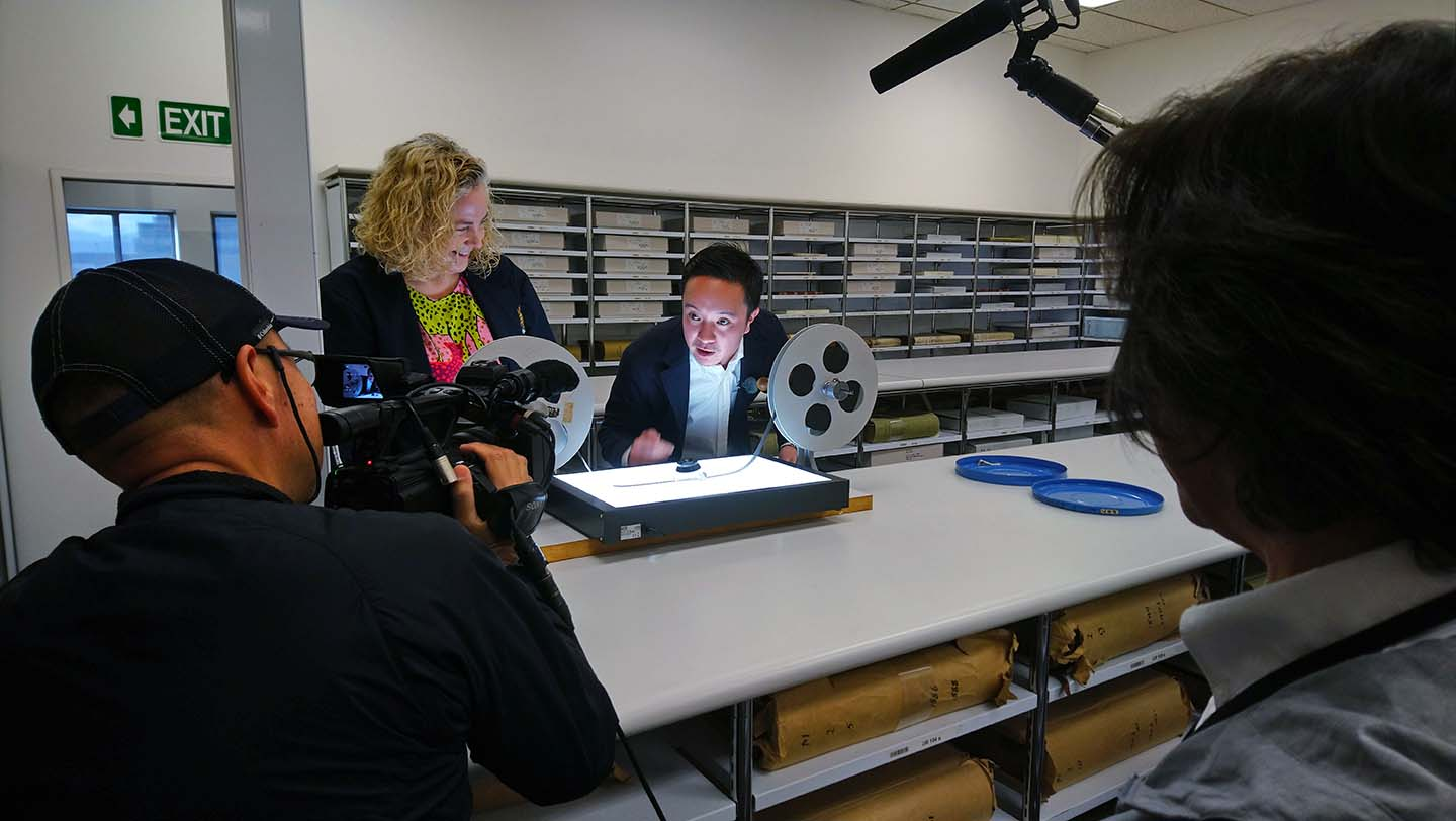 Gaku Hamada being shown reel to reel film over a lightbox by a preservation technician