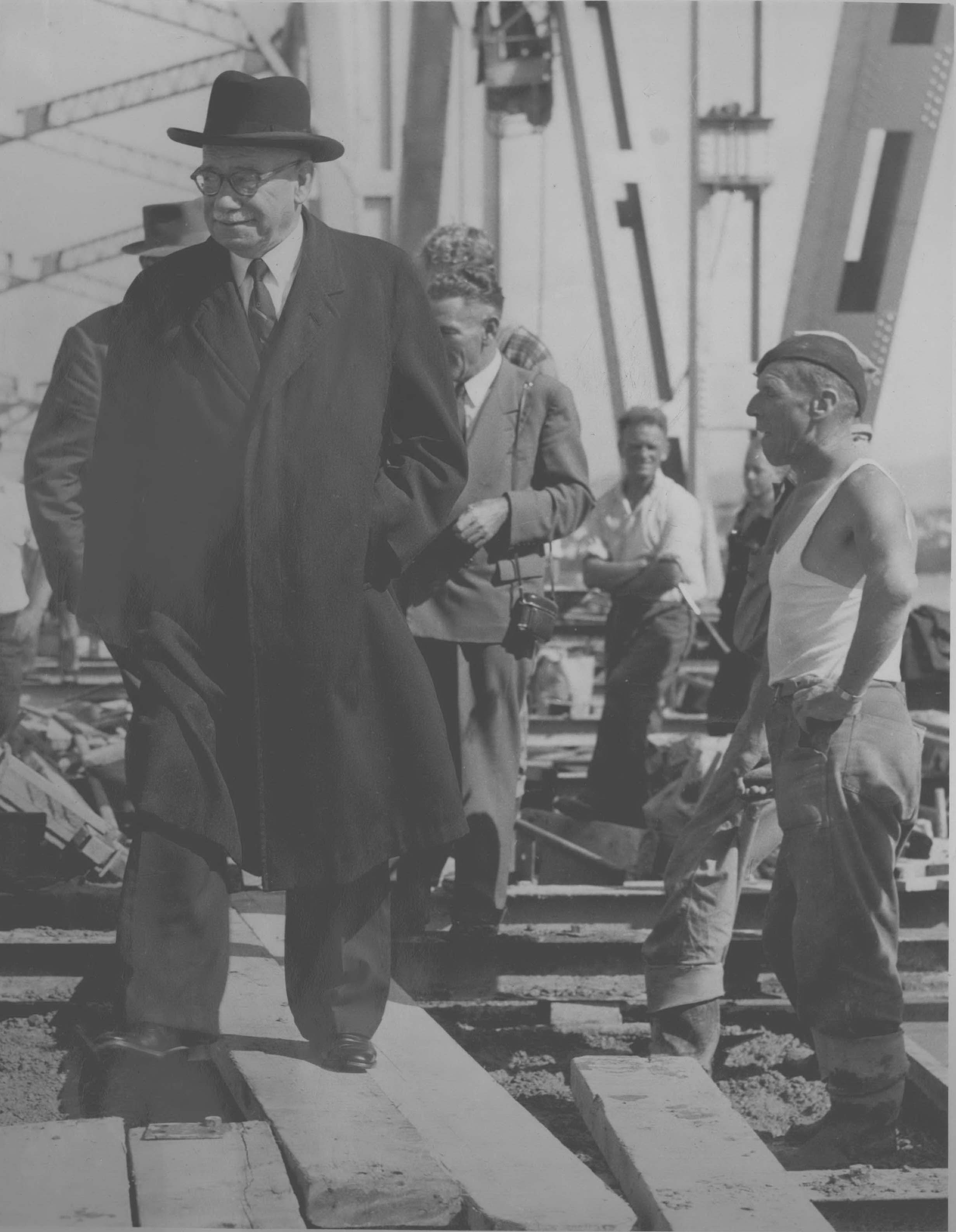 Sir John Allum crossing the complete Auckland Harbour Bridge with workers in the background