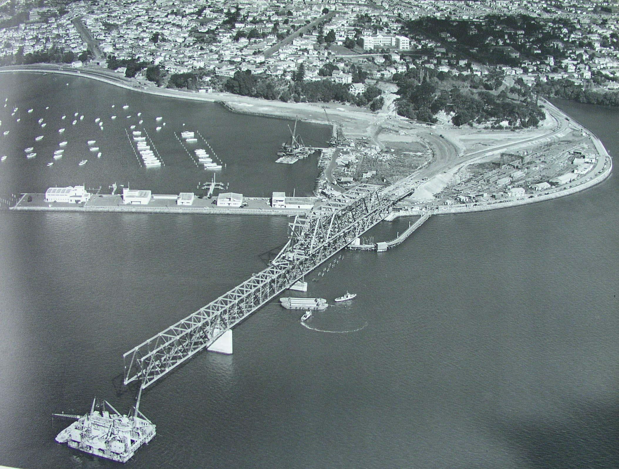 Aerial photo showing construction of Auckland Harbour Bridge from Point Erin