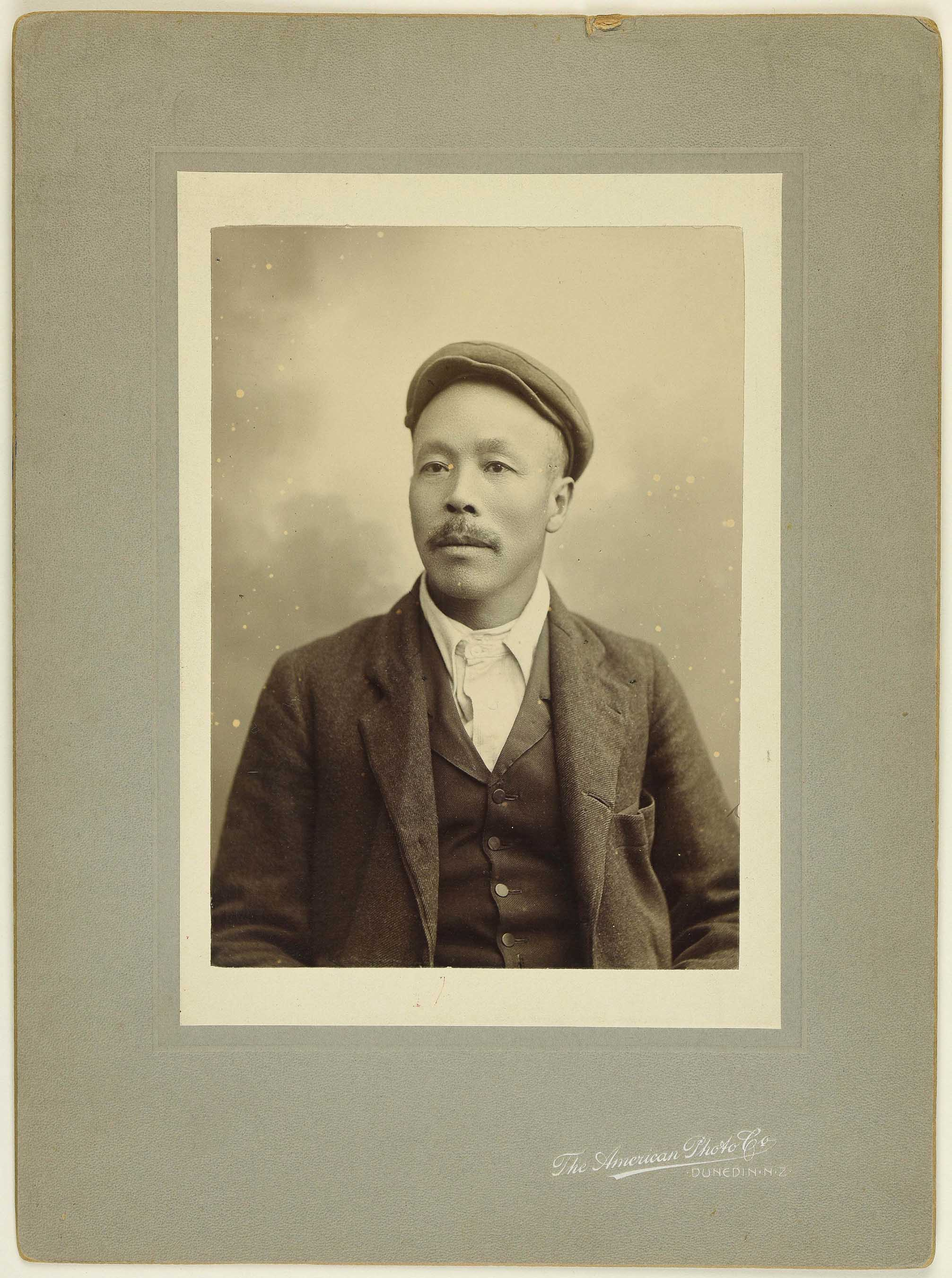 Sepia photo portrait of a Chinese man with moustache and flat cap