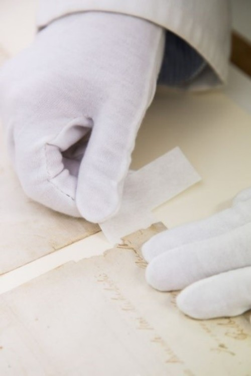 gloved hands attaching tape to a parchment scroll