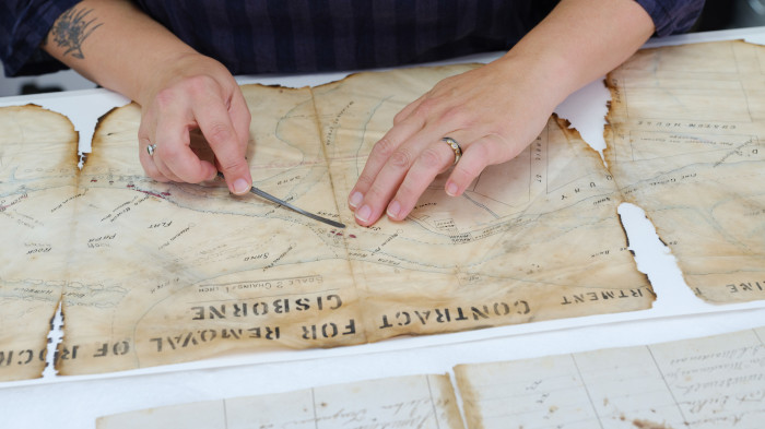 Hands scraping damaged material off an old map