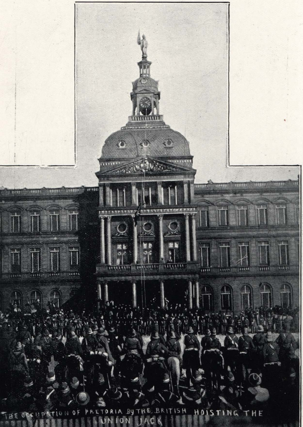 Black and white photo of cavalry outside a large building