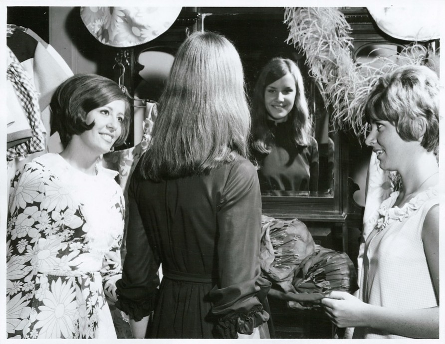 black and white photograph of girls standing around a mirror