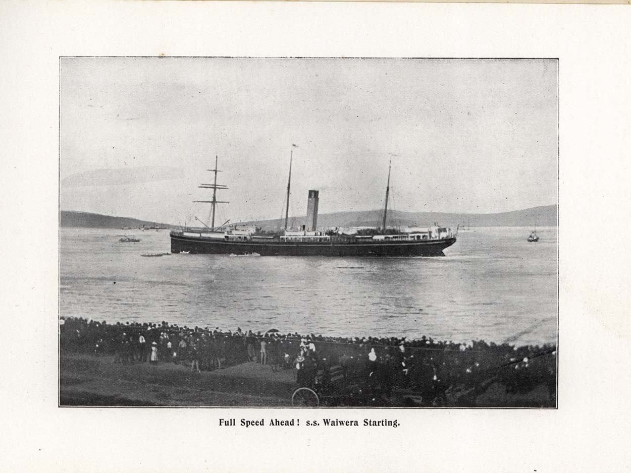 Black and white photo showing ship in harbour with people looking on from waterfront