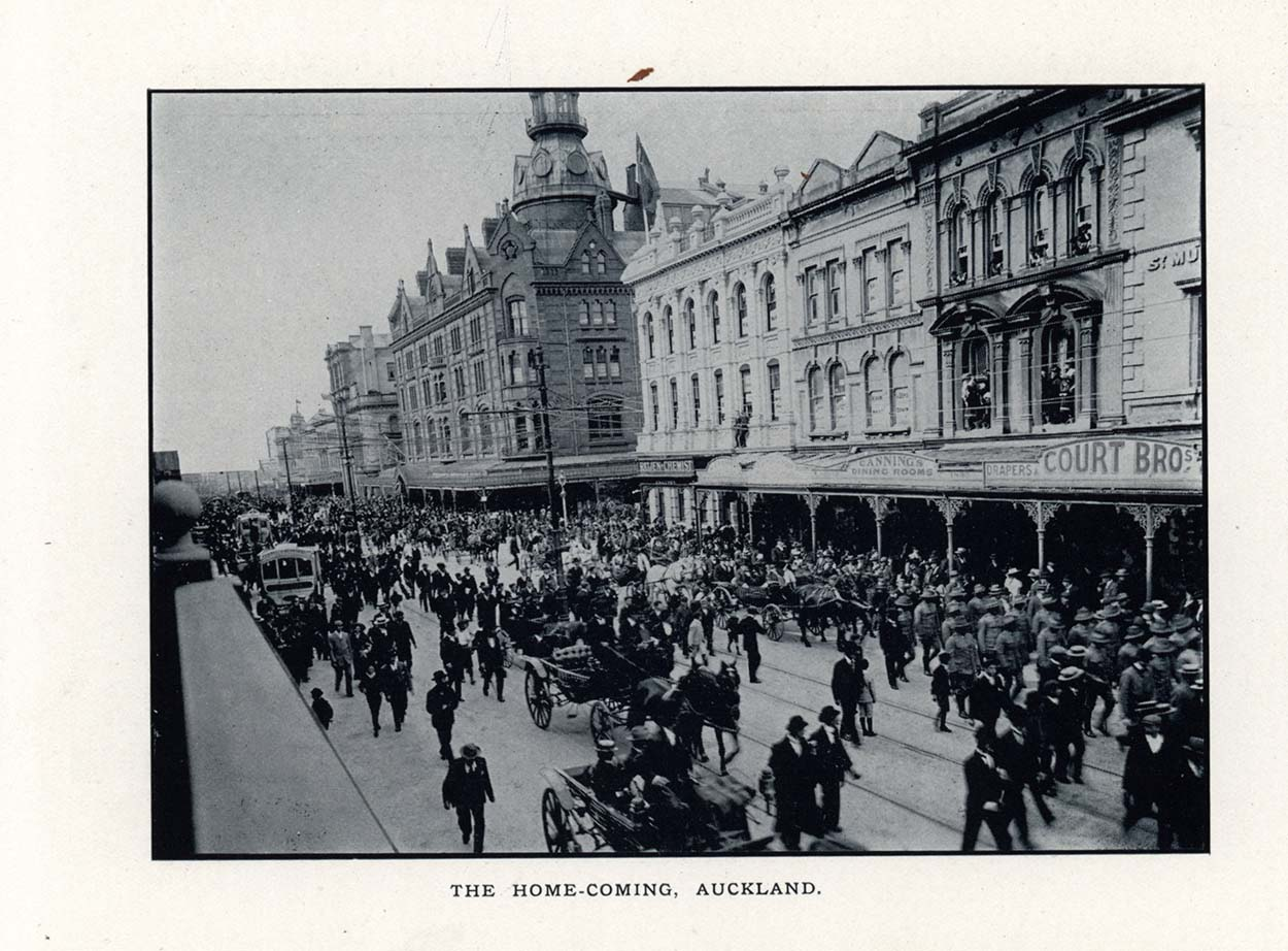 Black and white photo showing a procession walking down a street in Auckland