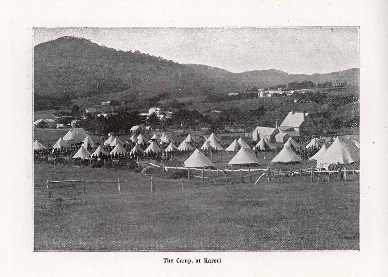 Black and white photo showing tents on a field with hill in the background