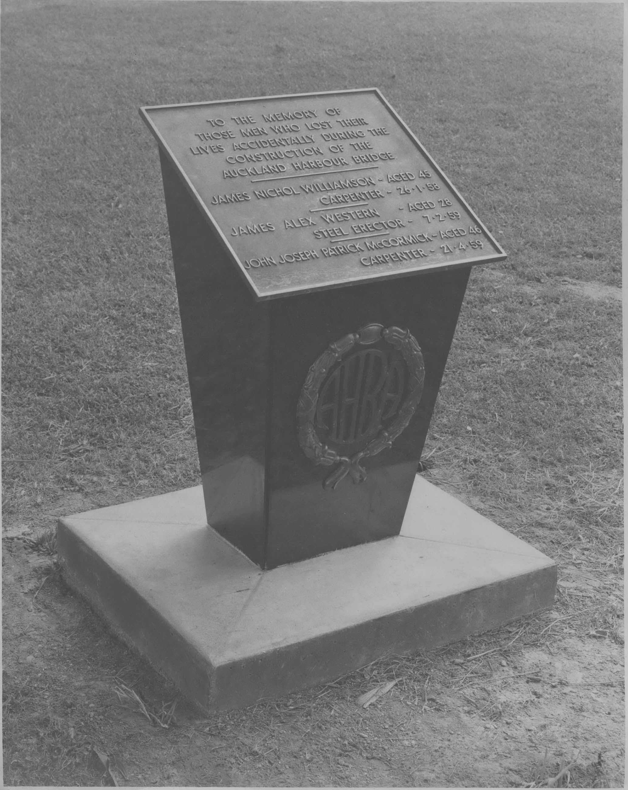 Black and white photo of the plaque remembering the three men who died during construction of the Bridge.
