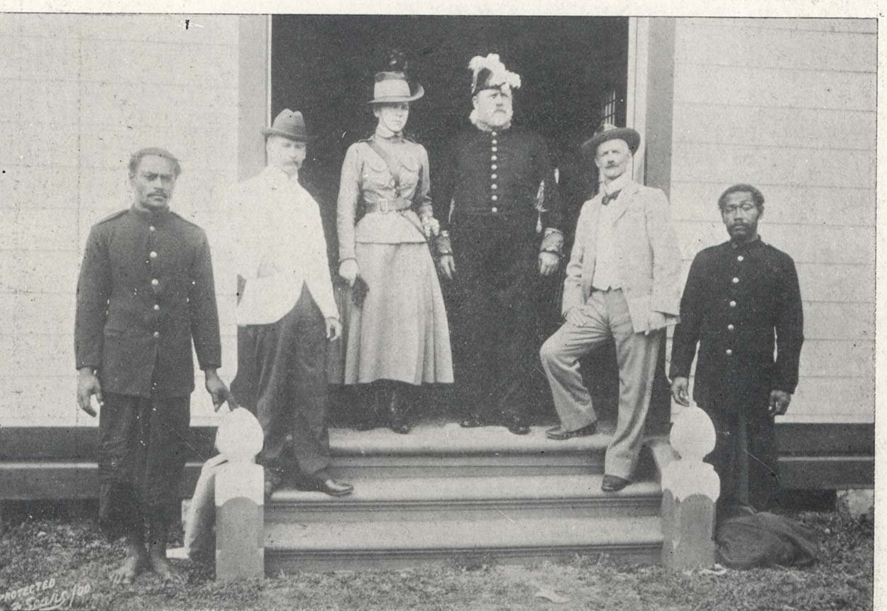 Black and white photo of a group of people standing on an entrance to a house