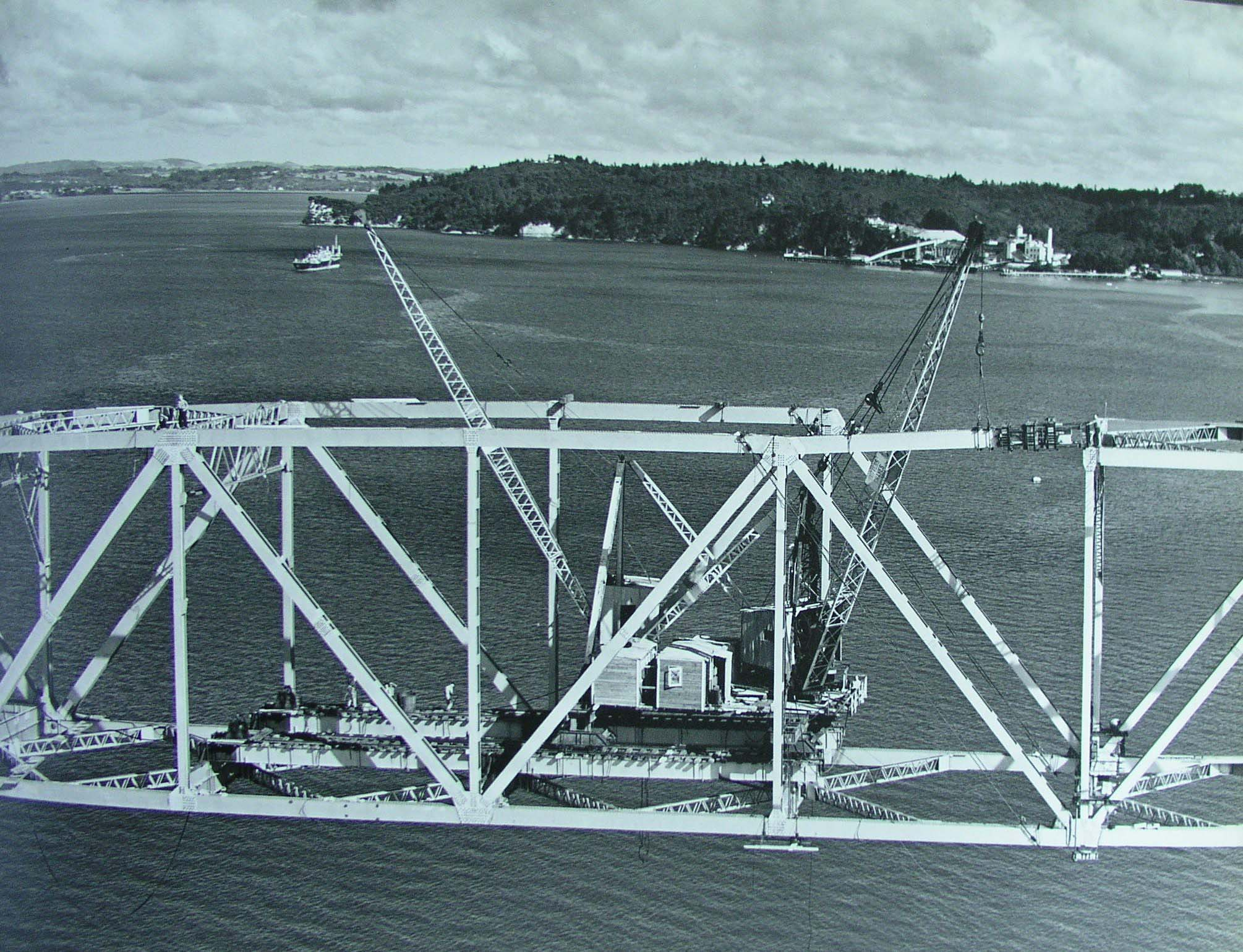 Aerial photo showing construction of Auckland Harbour Bridge on 9 March 1959. Girders being lifted.