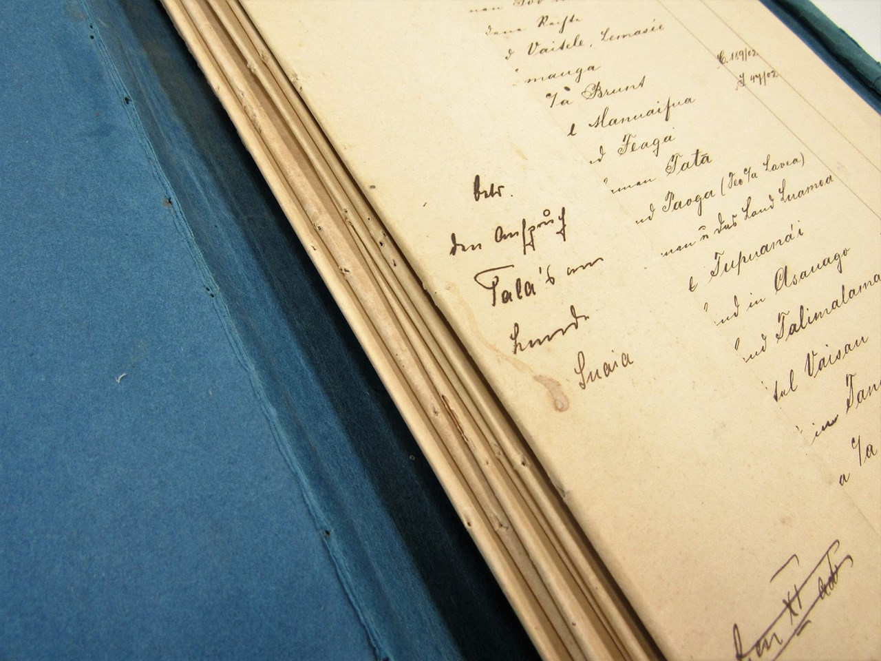 Photograph of pages the bound spine of an old register with hand written script