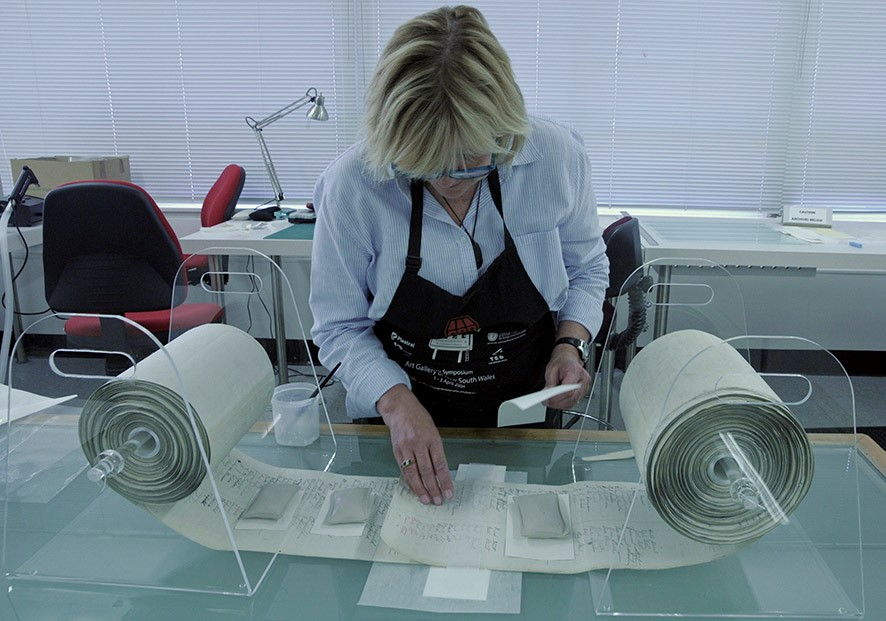 A woman working in a lab on a rolled up scroll
