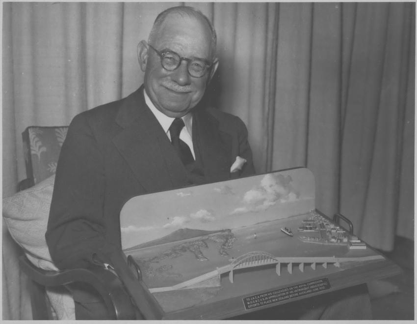 An image of Sir John Allum with model of Auckland Harbour Bridge