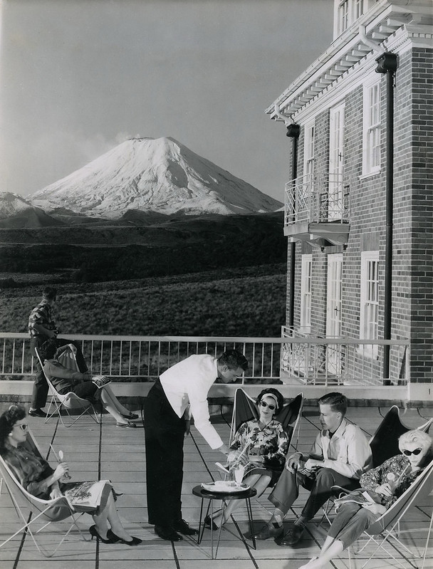 A waiter serving drinks on a balcony in front of a mountain