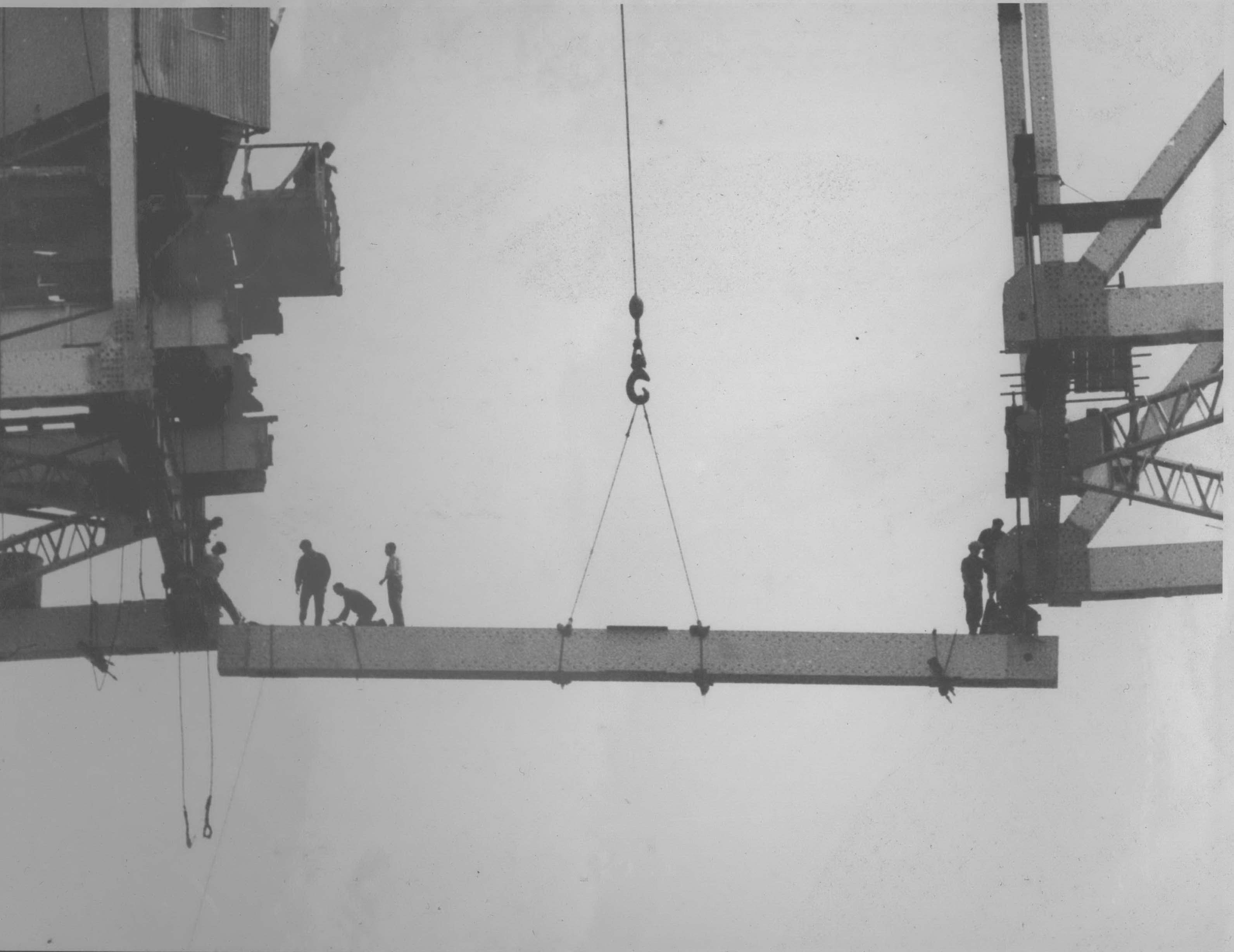 Male workers standing unassisted on a girder as it's being fitted.