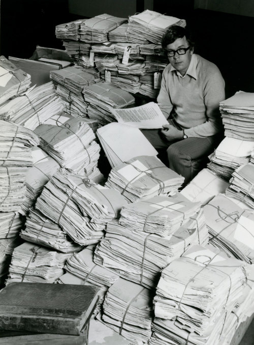 A man sitting surrounded by stacks of papers