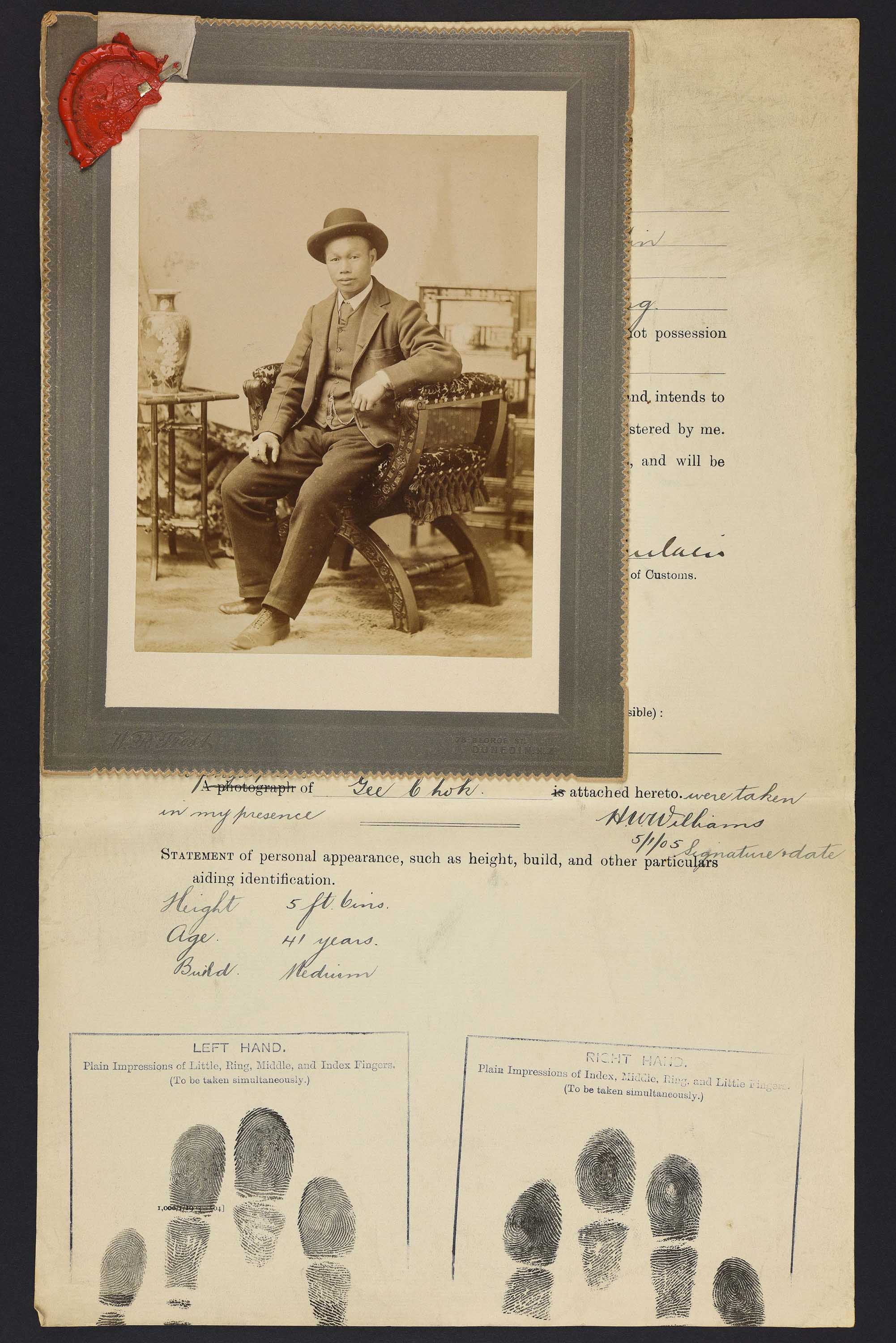 Sepia photo portrait of a Chinese man seated pinned to immigration papers
