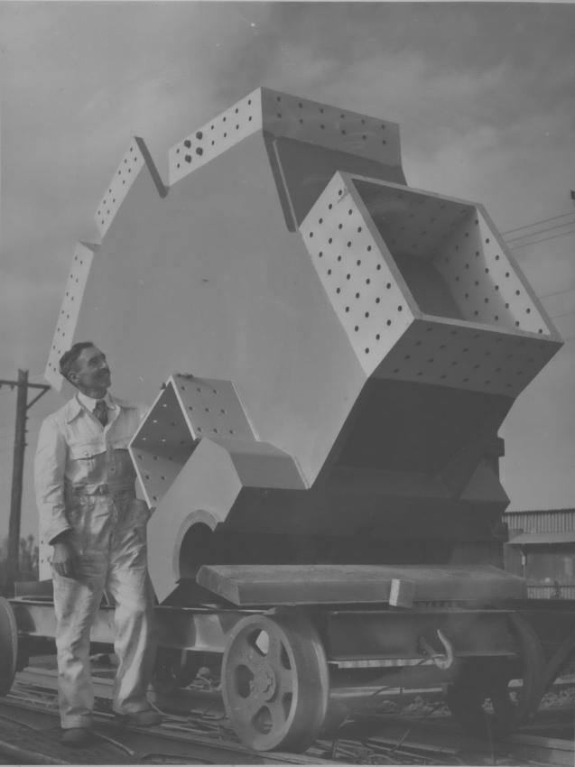 An image of a man and one of the knuckles used in the construction of the Auckland Harbour Bridge.