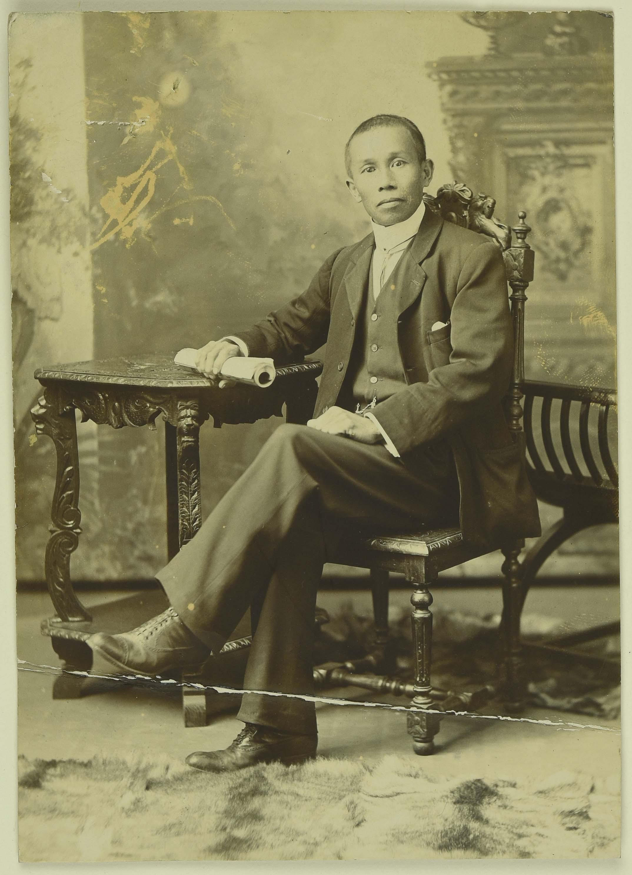 Sepia photo of a seated Chinese man resting his arm on a table.