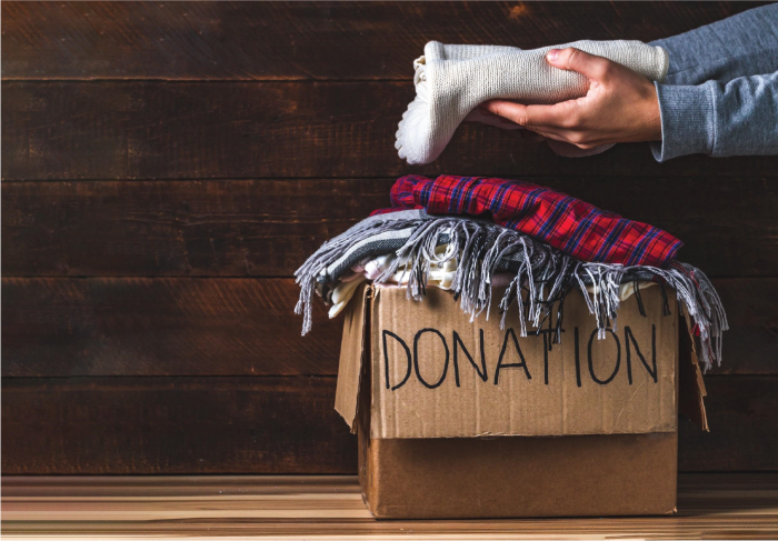 Person placing clothing in a cardboard donation box.