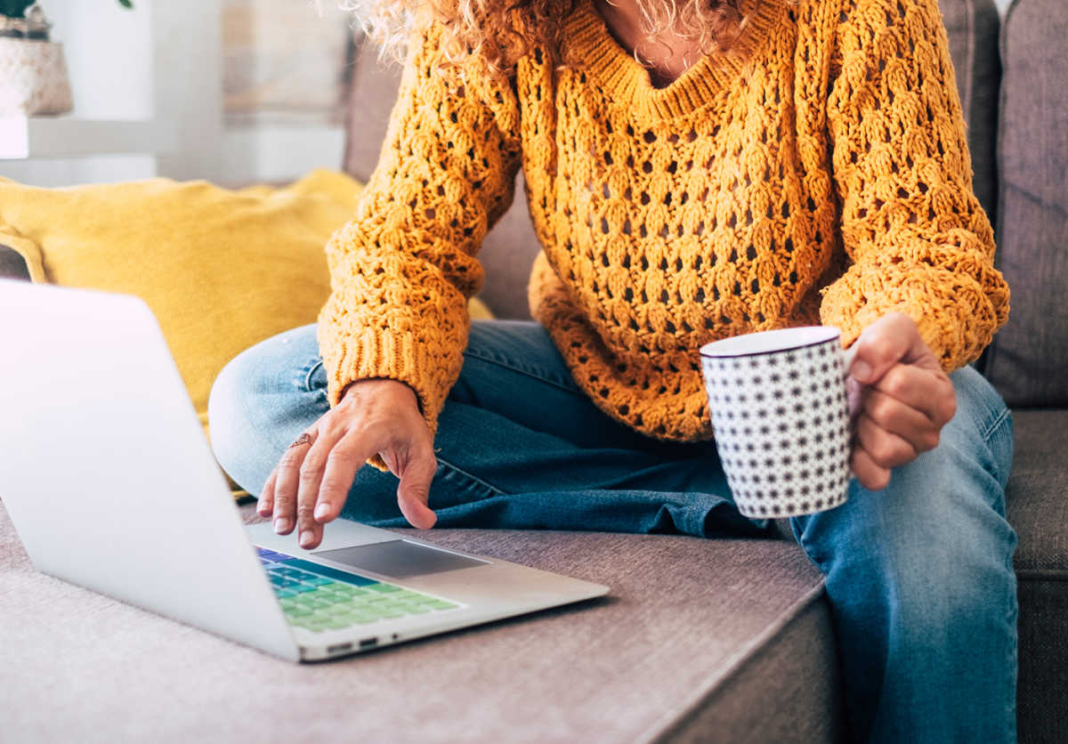 Woman sitting in on the couch working from home holding a mug.