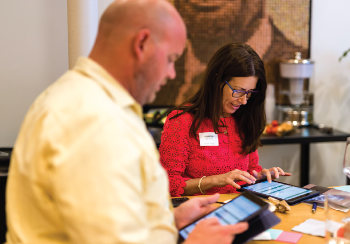 Man and woman sitting at a table participating in an interactive activity on iPads.