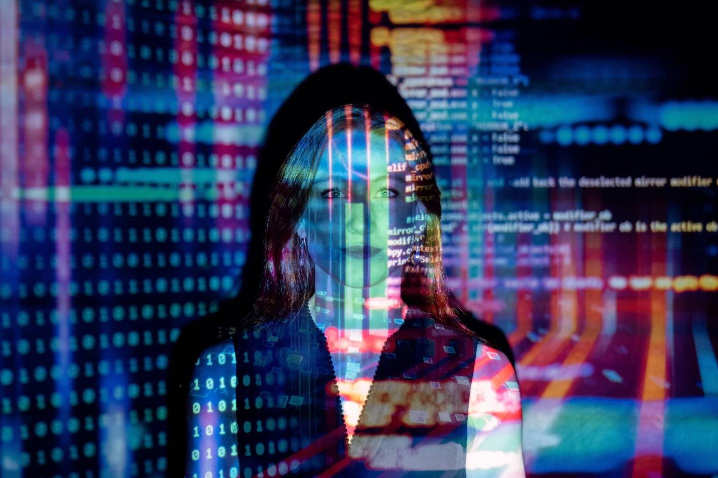 woman standing with programming picture projected on her