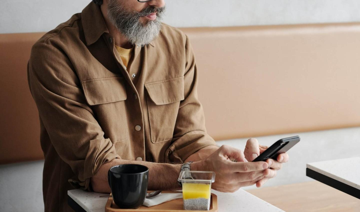 Man using his phone while in a modern cafe