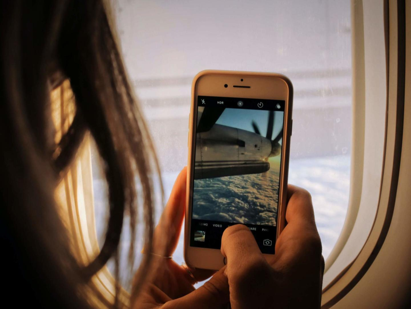 a girl is in a plane taking a photo on her phone
