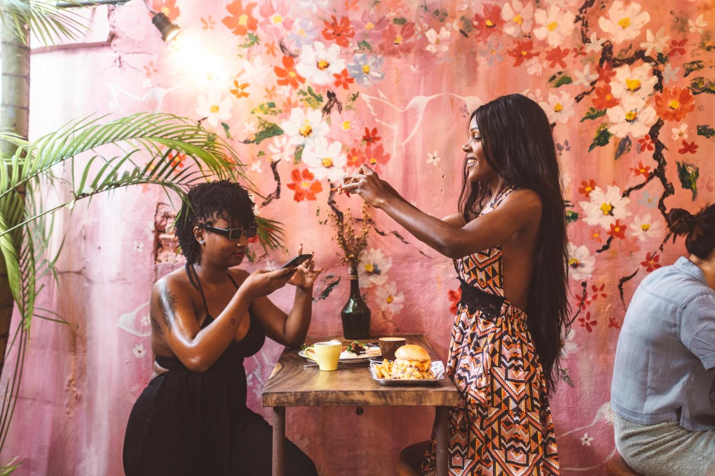 2 women taking photos of their food in a pink and flowery restaurant