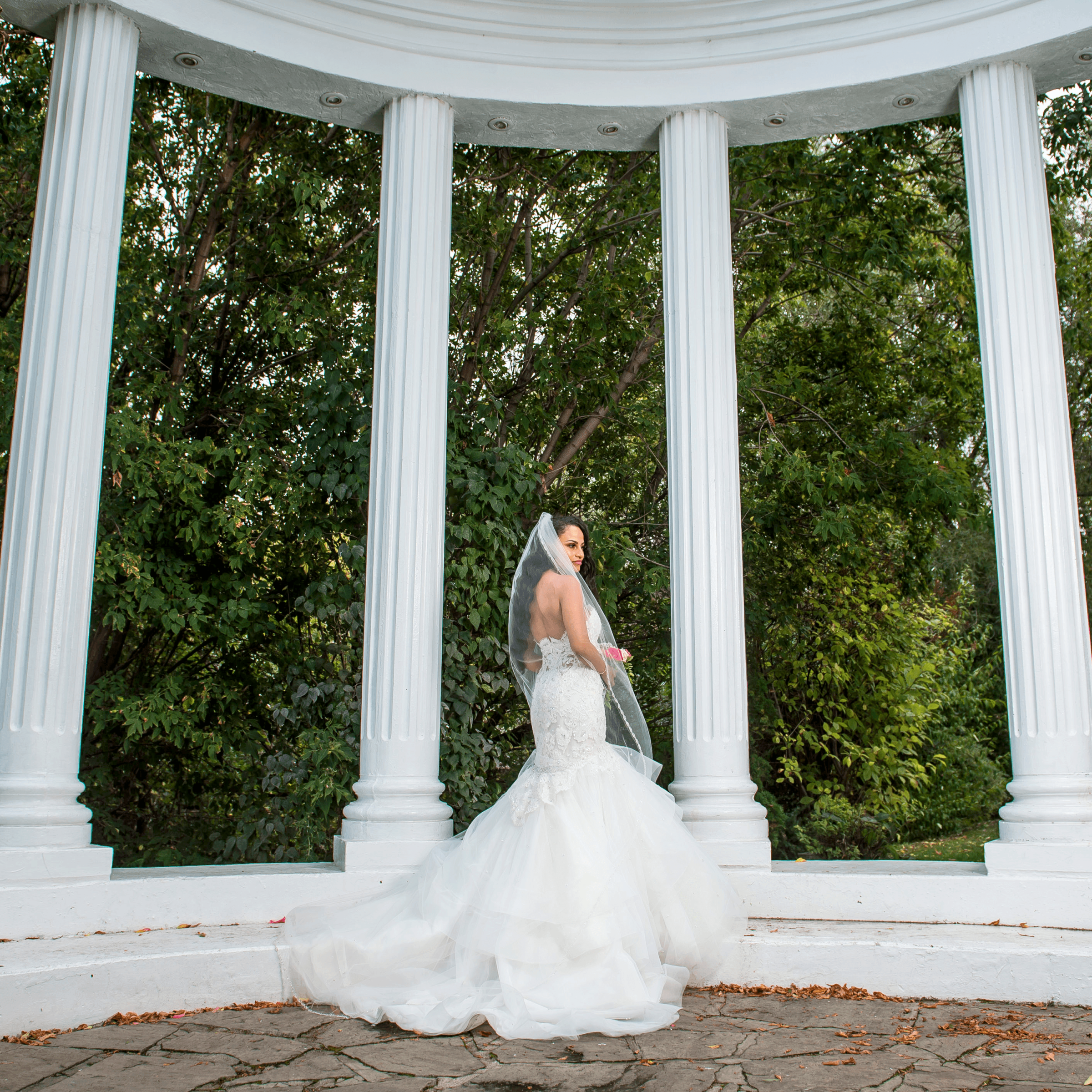 A bride standing in the Paradise Banquet Halls garden venue's columned area with lush, green trees in the background.