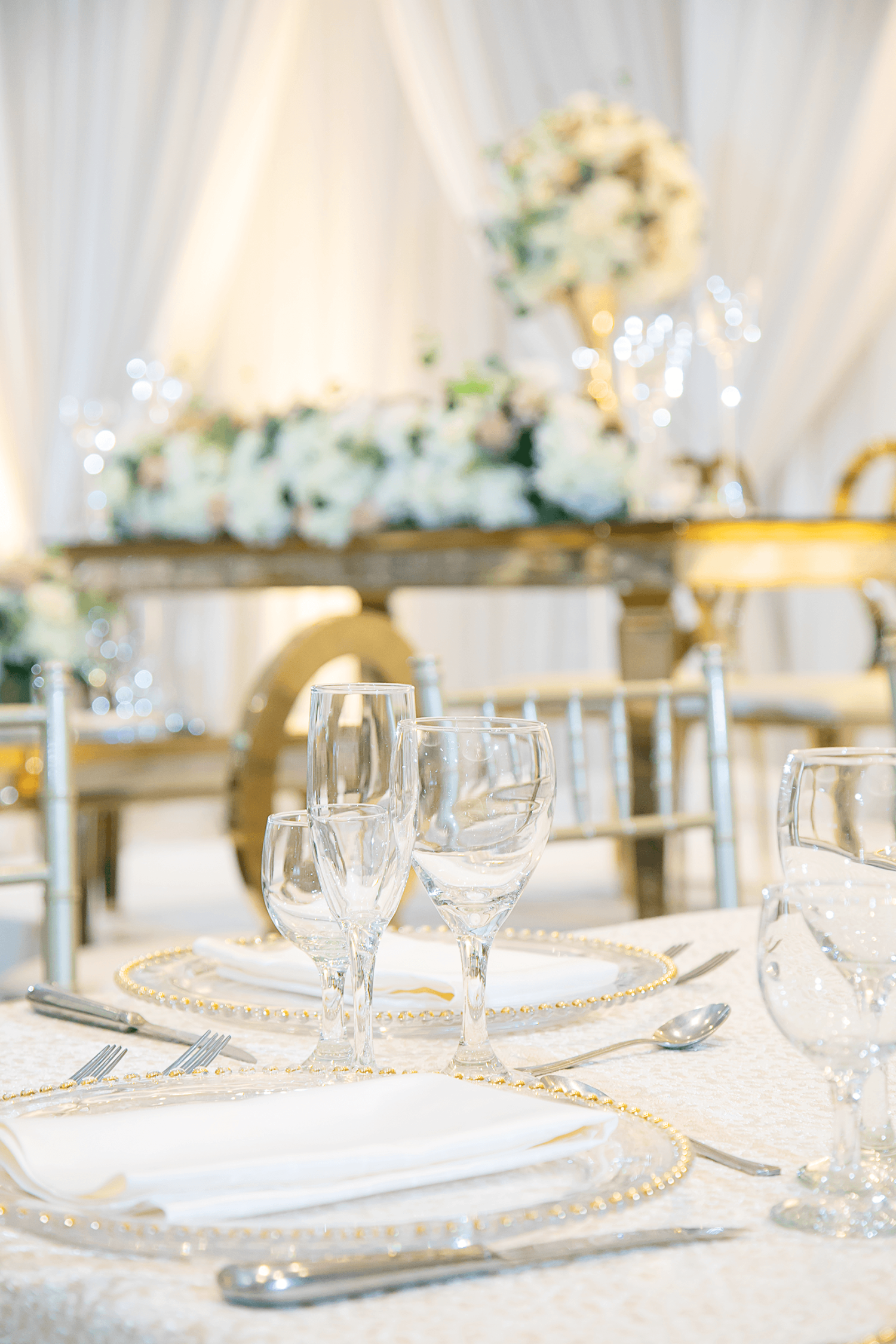 A close up of a table setting at a wedding with white and gold accents at Paradise Banquet Halls.