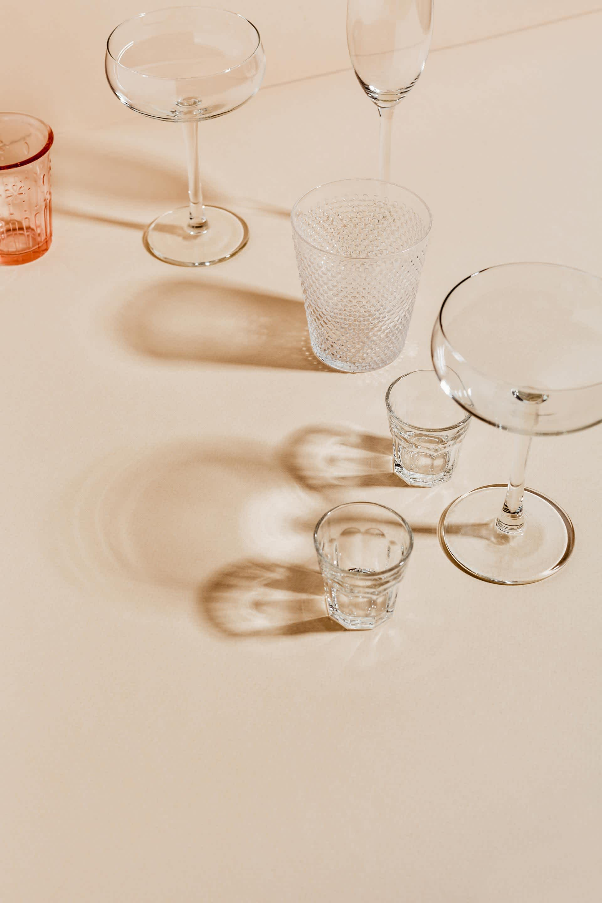 Various sizes and types of drinking glasses on a pink background