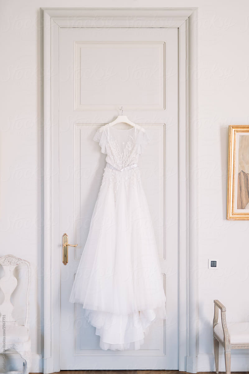 A white wedding dress hung on the back a closed door.