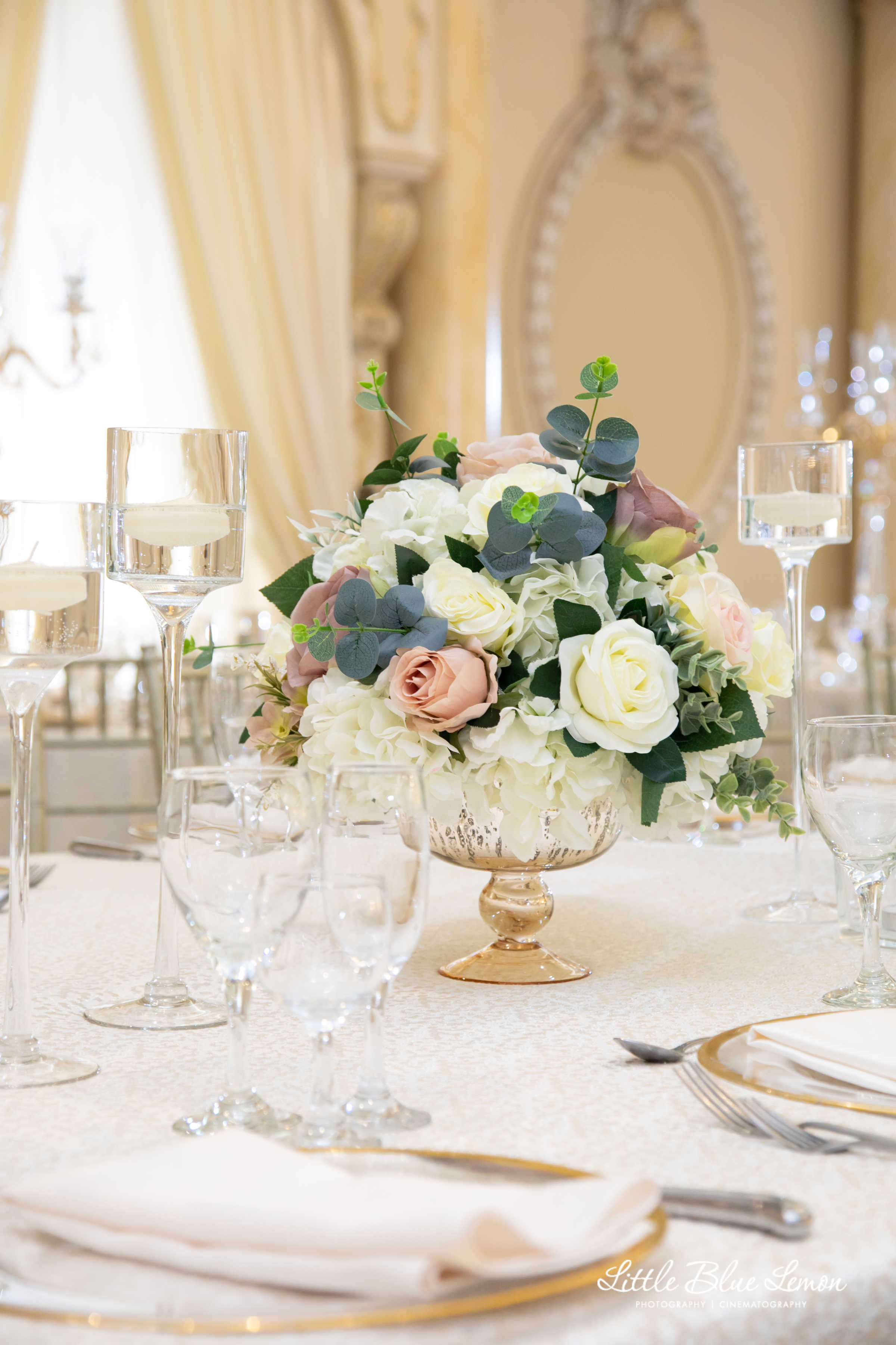 A flower arrangement set on a table with silverware and a white linen table sheet.