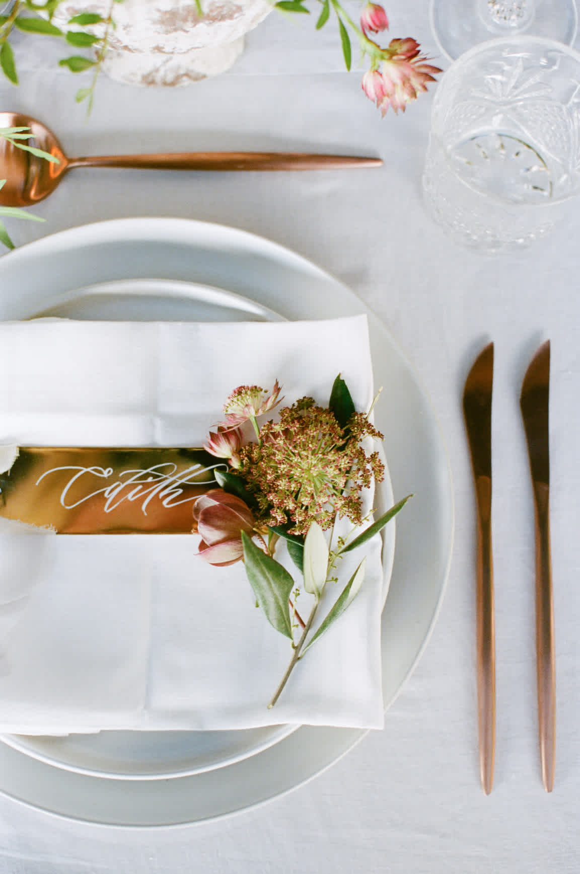 A top-down view of table setting with plates, knives, spoons, napkins, drink glasses, and a floral arrangement.