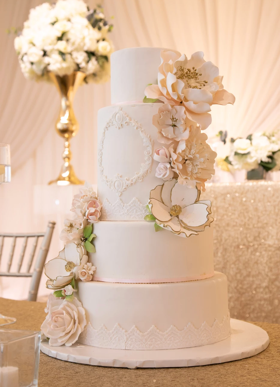 A white, 4-tier wedding cake decorated with flowers.