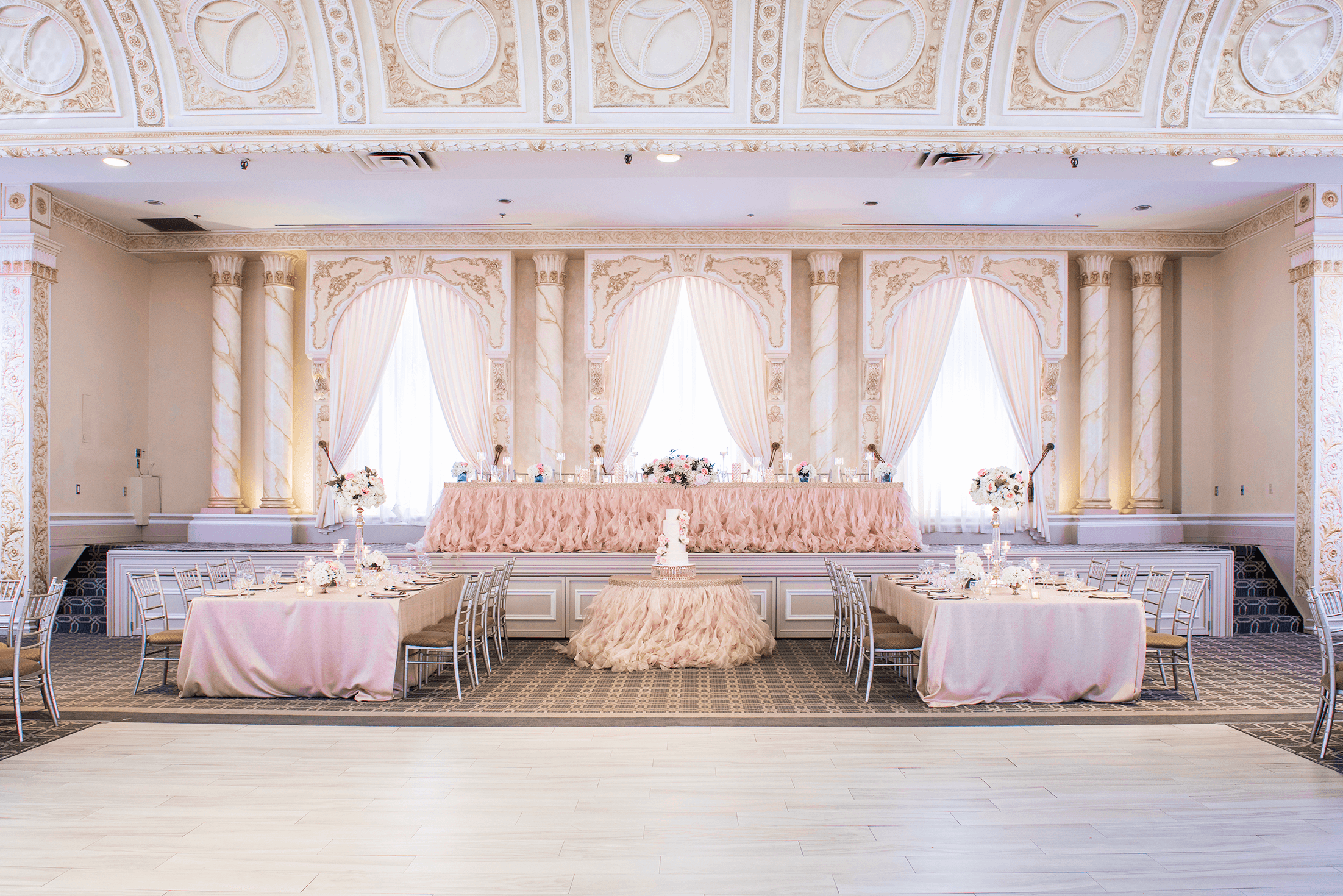 The pink-themed head table at a wedding in a ballroom with a dance floor.