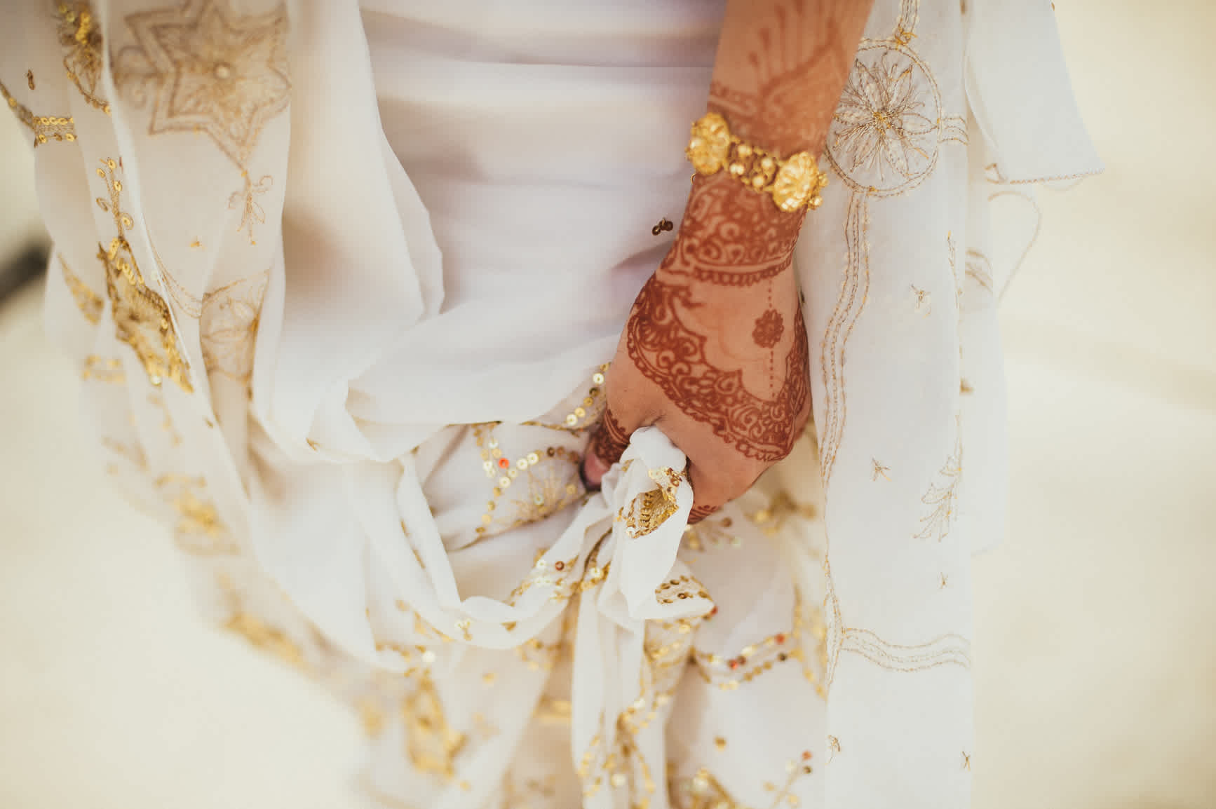 A close-up of a woman in a wedding dress with henna on their arm and hand.