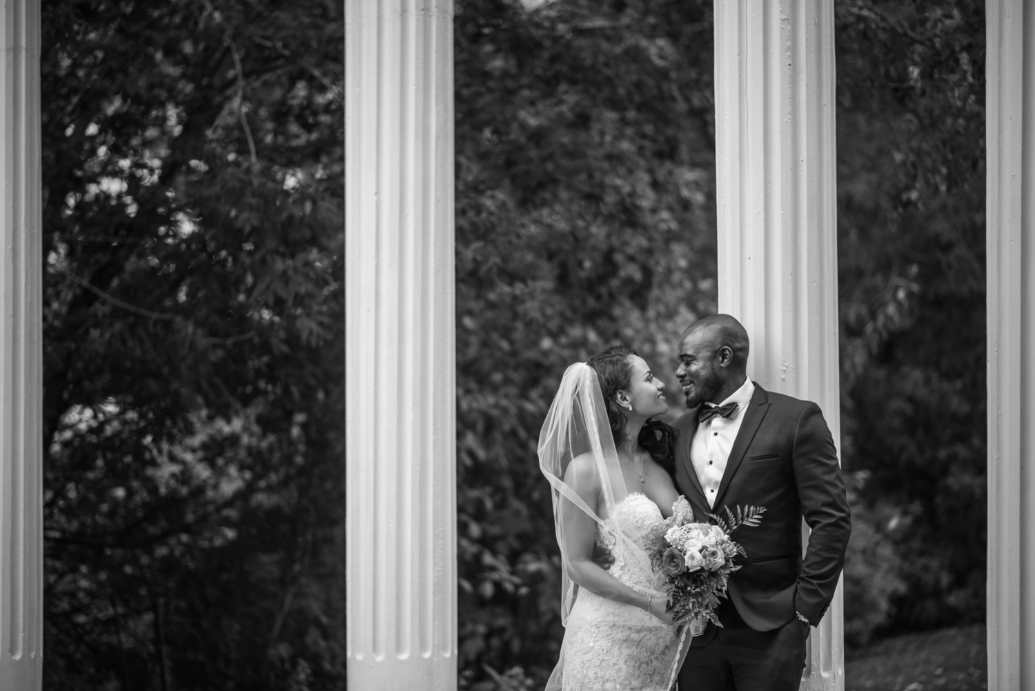 The happy couple, John and Veronica, standing outside, in front of white columns, in a black and white photo.
