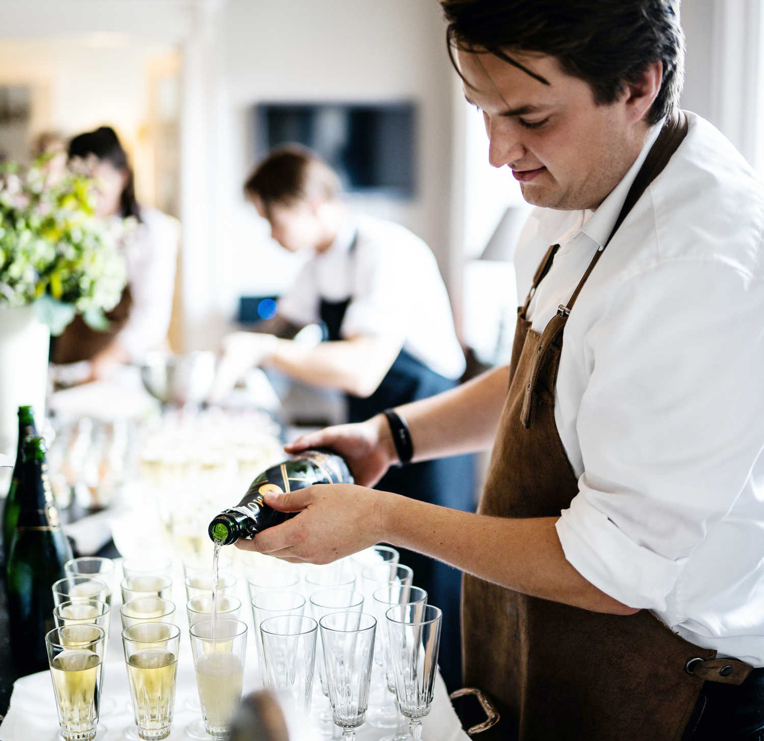 A staff member of Paradise Banquet Halls pouring champagne into glasses to be served at a wedding