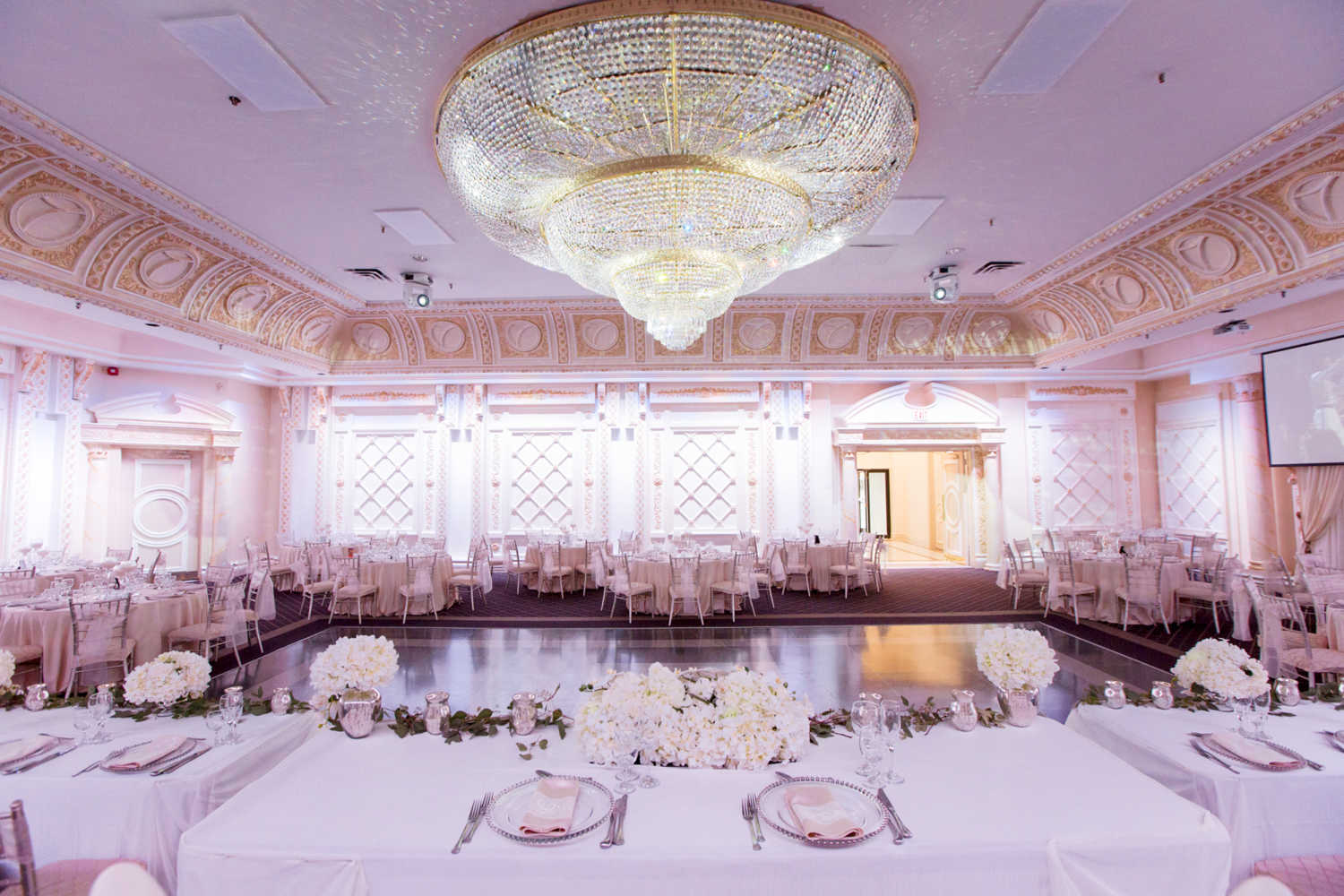 The Queen Victoria Wedding venue at paradise banquet halls with table settings, a large dance floor and a giant chandelier.